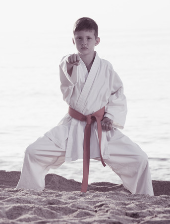 Young boy training karate positions at ocean beach