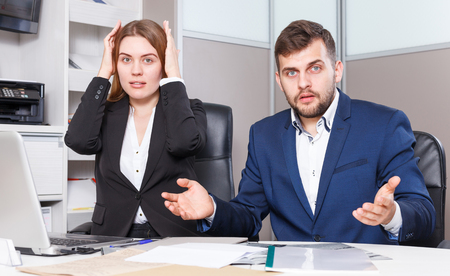 Portrait of worried young salespeople working on laptop in furniture showroom  Stock Photo