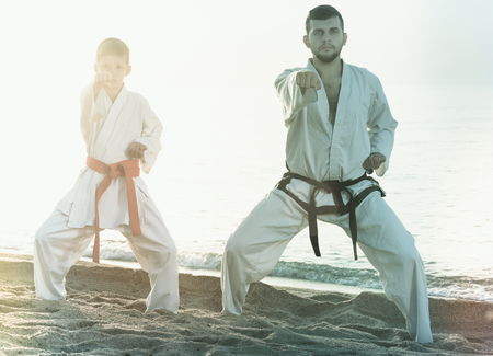 Man and boy in uniform doing karate poses at sunny sea beach Stock Photo