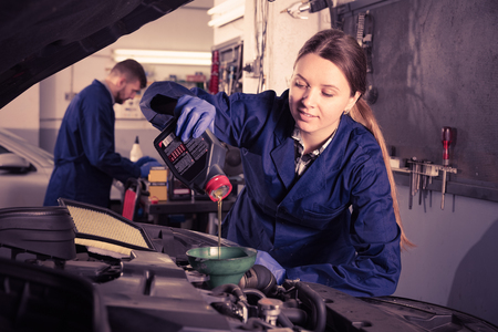 adult smiling female is standing near car and replacing the oil in workshop. Stock Photo