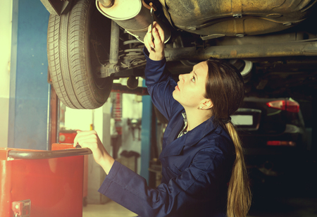 young female is standing near car and repairing it in workshop. Stock Photo