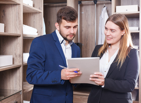 Young female and male sales managers of furniture salon standing with papers in display dressing room Stock Photo