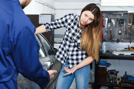 Young woman is disappointed of tire replacement of her car in spring in workshop.