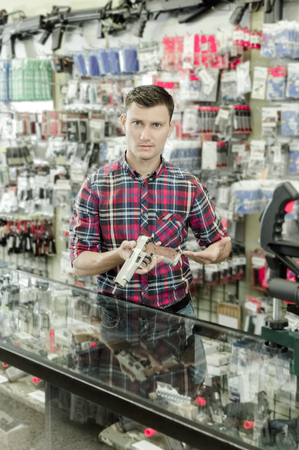 Cheerful salesman displayed variant of air weapon in airsoft shop Stock Photo