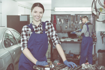 Young female master is standing near her workplace in workshop