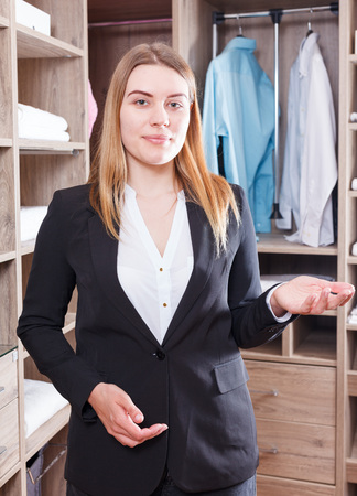Smiling female seller showing comfortable furniture for clothes room in salon