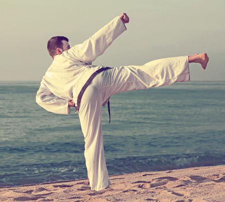 Young  man demonstrates aikido poses at seaside in sunset outdoor