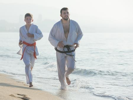 man and teenagerl in a kimono run on the seashore