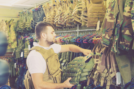 Young positive italian guy choosing flak jacket in military shop