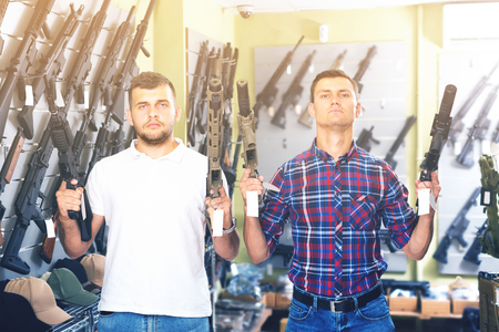 Men 20-30 years old are choosing pneumatic rifle in airsoft store.