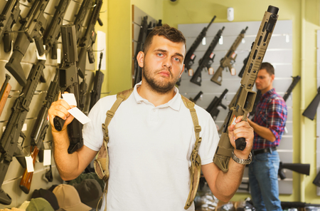 Two young men selecting pneumatic weapon in military store