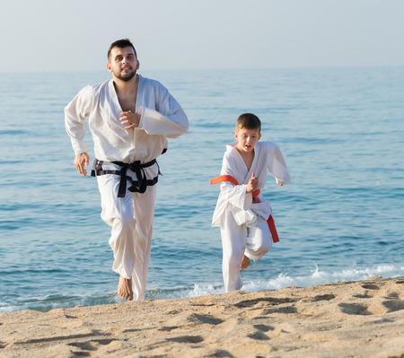 coach and pupil in a kimono run on the seashore