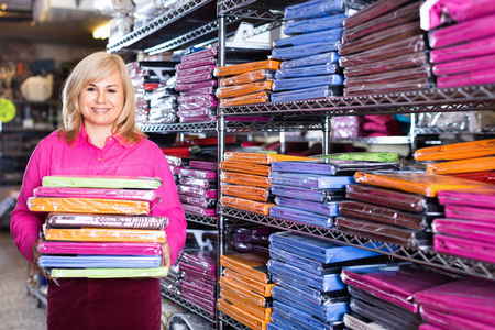 Portrait of cheerful glad mature woman showing stack of bedsheet in the textile shop