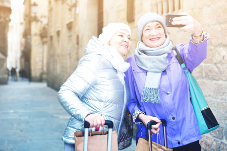Happy elderly women tourists making selfie with phone during walk around city