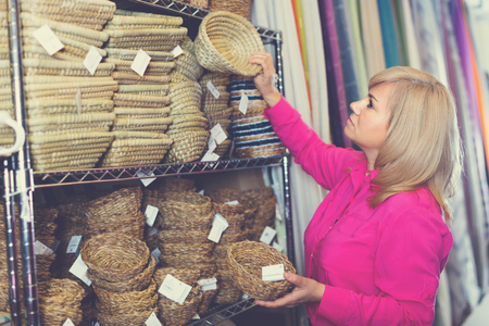 Happy cheerful  woman standing with wicker basket for decoration home in furniture store
