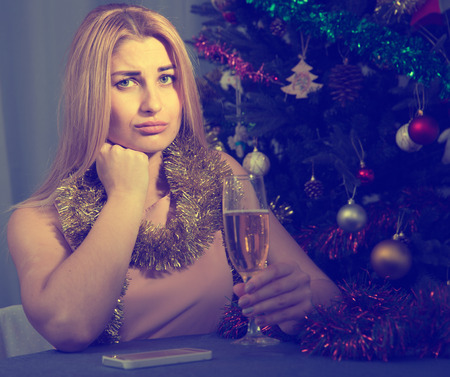 Sad woman is bored with champagne in New Year night at home.