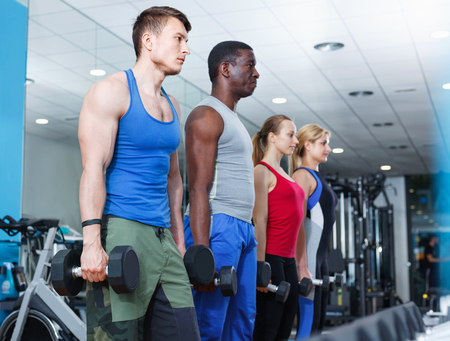 Portrait of athletic glad  friendly young people doing exercises with dumbbells in gym