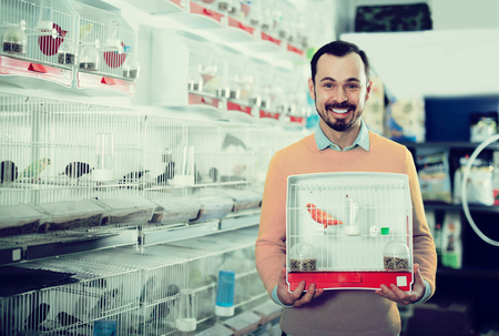 Young happy man enjoying his purchase of canary bird in pet shop