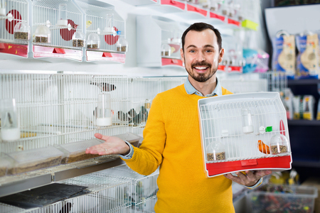 Young happy male customer boasting his purchase of canary bird in pet shop