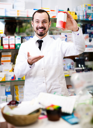 Smiling male pharmacist offering reliable drugs in pharmacy