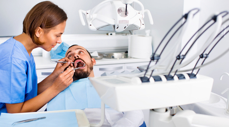 Diligent  smiling positive stomatologist girl in uniform is taking visional inspection of a man on the chair in dental clinic. Standard-Bild