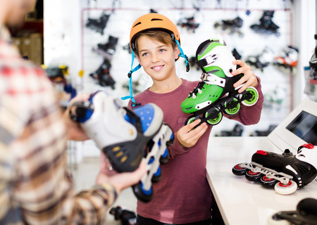 happy male shop assistant helping positive american boy to choose roller-skates in sports store