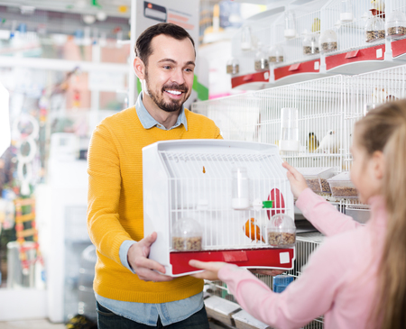 Man seller offering cage with canary bird to girl in pet store