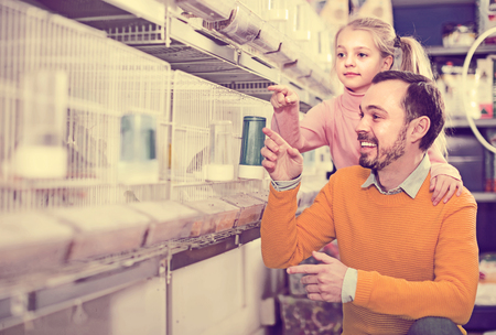 Smiling father and girl deciding on best bird to keep in pet shop Foto de archivo