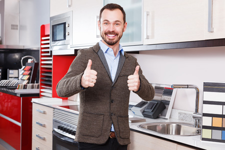 Portrait of happy male standing in shop of kitchen furniture