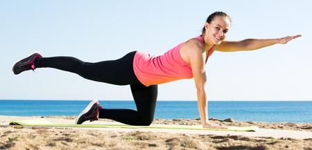 Attractive woman exercising yoga at sea beach outdoor Stockfoto