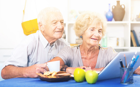 Portrait of cheerful mature spouses using laptop at home
