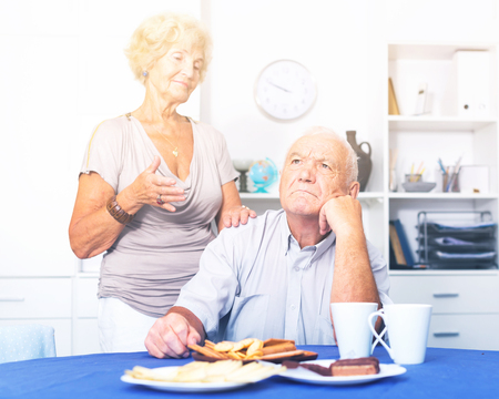 Mature lady trying to calm her male friend and apologize after dispute  Stock Photo