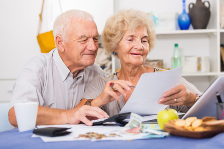 Portrait of happy senior spouses with bills and laptop while sitting at table at home Фото со стока