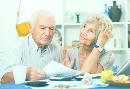 Frustrated senior couple faced financials troubles at table with bills, money and calculator