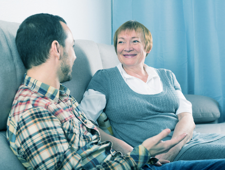 Aged mother and son are friendly conversation sitting at home on sofa