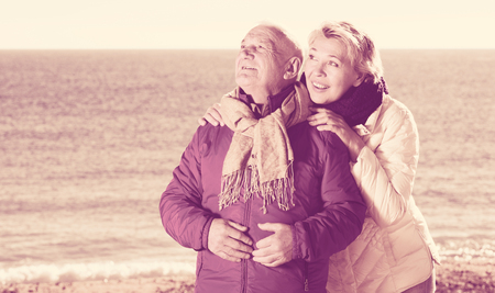 Aged husband and wife taking stroll on beach and watching skies Stock Photo