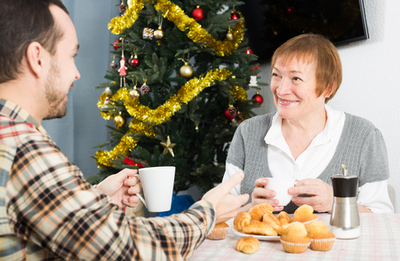 Smiling mature mother and son having breakfast at festive Christmas table