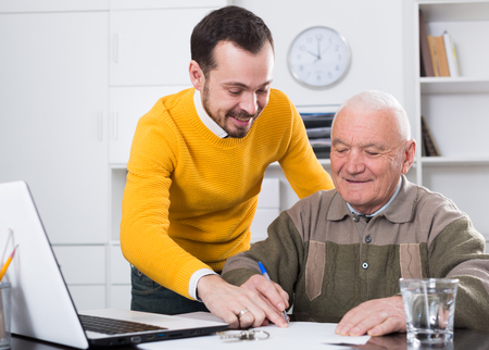 Elderly man and young agent sign lease contract of apartment at office