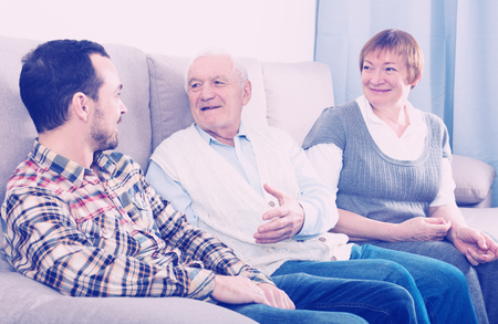 Mature mother and father and son happy to spend time together at home Stock Photo