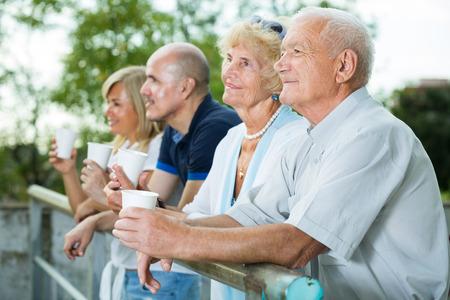 elderly parents with older children  drink tea at plastic cup in the garden