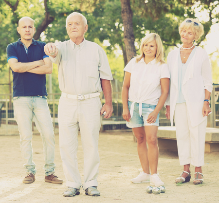 Happy elderly people playing bocce in the park