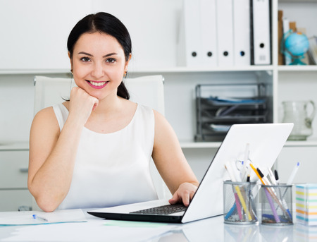 Young woman worker posing gracefully while working in office