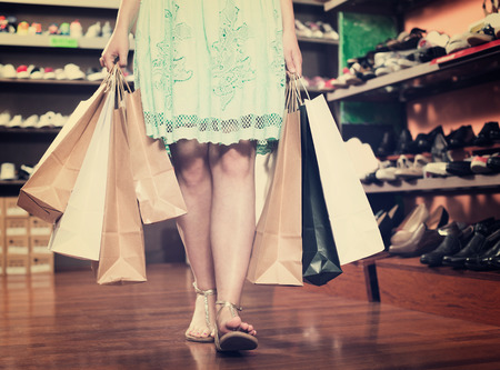 Happy woman is going out of the fashion store with full hands of purchases