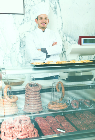 Happy adult ordinary man seller working at meat market Stock Photo