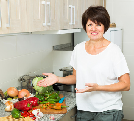 positive mature woman serving fresh salad on kitchen indoors