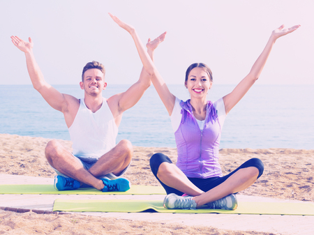 Friendly smiling woman and man sitting cross-legged do yoga poses on beach at daytime