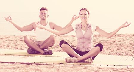 Positive cross-legged guy and girl training yoga poses on seaside Stock Photo