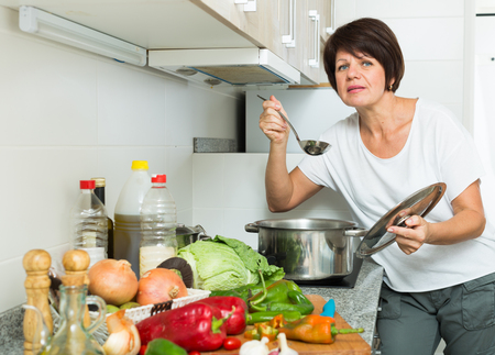 positive retiree woman holding cooking pot on kitchen indoors