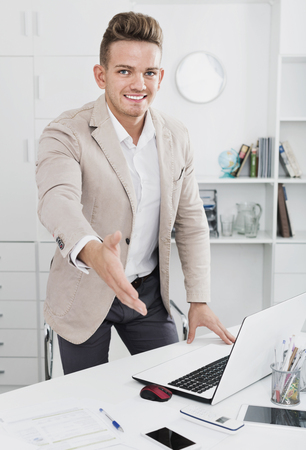 Happy  friendly businessman offerring hand for greeting in office interior Stock Photo