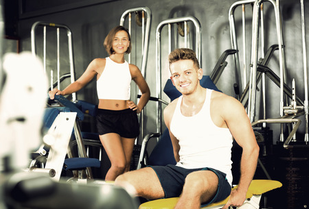 Portrait of smiling well trained young man sitting on bench between exercises in gym